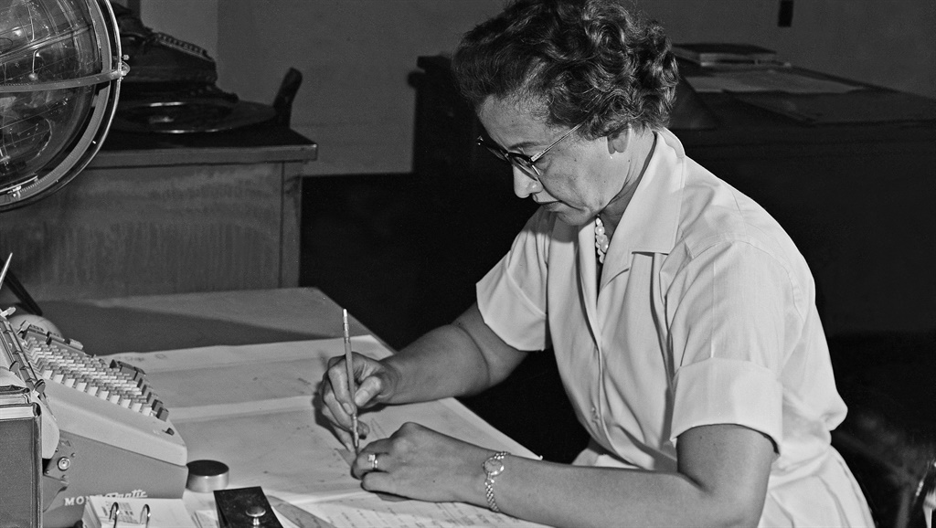 NASA space scientist and mathematician Katherine Johnson poses for a portrait at her desk with an adding machine and a Celestial Training device at NASA Langley Research Center in 1962. (Photo by NASA/Donaldson Collection/Getty Images)
