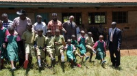 Ahadi Kenya director Stanley Kamau, in a photo with pupils of Kairuthi Primary School he donated shoes to them. (Photo by Joseph Njung'eh)