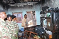 Administration Police officers looks on one of the rental houses which were razed down by fire at Majengo slums, Ruring'u estate in Nyeri county.