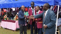 The principal of Ihithe Secondary School (far right) with student leaders receives a success-wishes card from Tetu MP Ndung'u Gethenji. (Joseph Njung'eh)