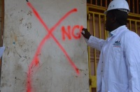 An NCA  official marking a building as unfit in Nyeri town.
